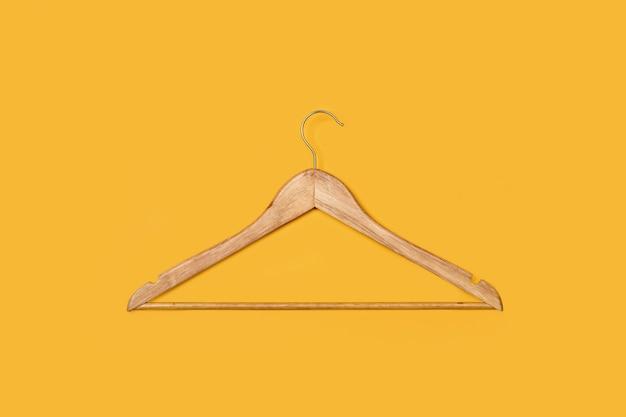 黄色の背景に1つの木製ハンガー