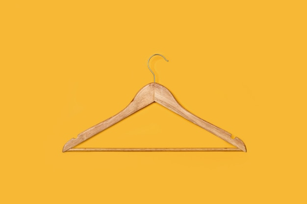 One wooden hanger on a yellow background