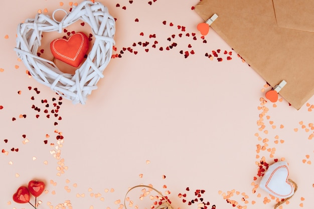 One wooden white  heart and envelope with red ribbon near beads with hearts on pastel pink colors.