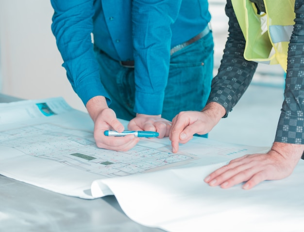 Один рабочий показывает важные детали в архитектурном плане проекта другому.