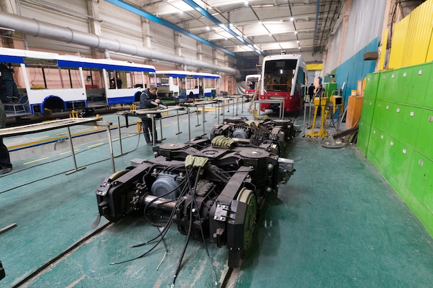 One working day of modern automatic bus manufacturing with unfinished cars automotive parts workers in protective uniform
