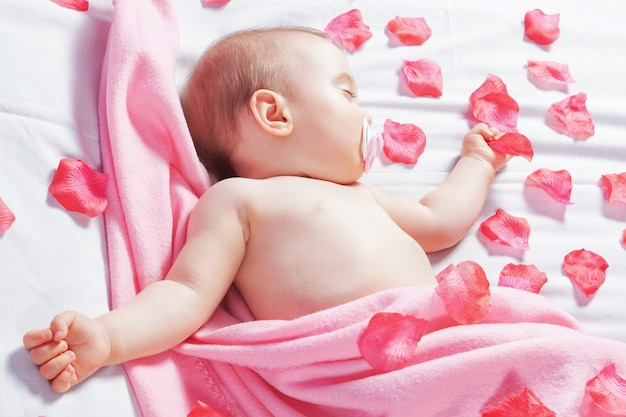 The one-year baby sleeping and wrapped pink flower petals. covered with a pink blanket.