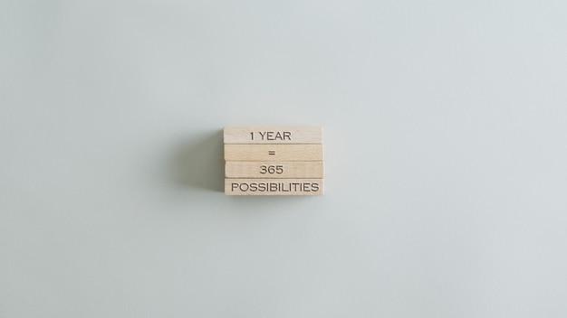 1 년은 나무 못 더미에 365 가능성 표시입니다. 베이지 색 테이블 위에