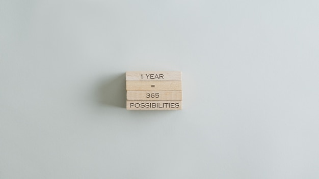One year is 365 possibilities sign on stack of wooden pegs. over beige table