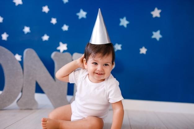 Годовалый мальчик празднует день рождения возле серебряных букв one на синем фоне со звездами.