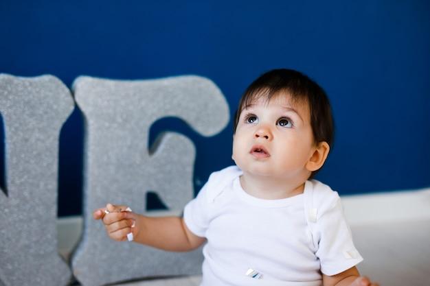 한 살짜리 아기는 별과 파란색 배경에 은색 문자 one 근처의 생일을 축하합니다.