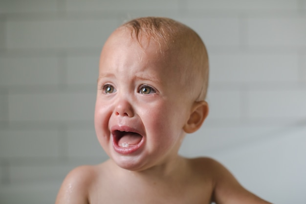 One-year-old baby cries close-up in the bathroom