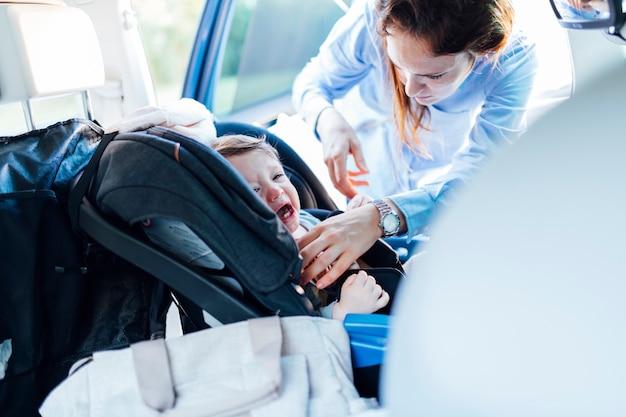 母親と呼ばれるチャイルドシートに座って手に負えないほど泣いている1歳の赤ちゃん