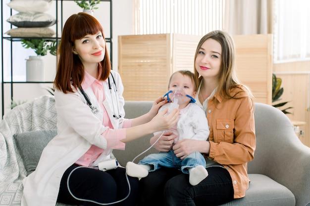 医者からネブライザー治療を受けている1歳の女の赤ちゃん。蒸気ネブライザーを通して呼吸。吸入療法装置のコンセプトです。