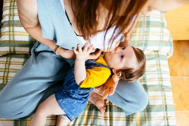 한 살짜리 아기가 집에서 침대에서 어머니의 젖을 빨고 있습니다. 모유 수유