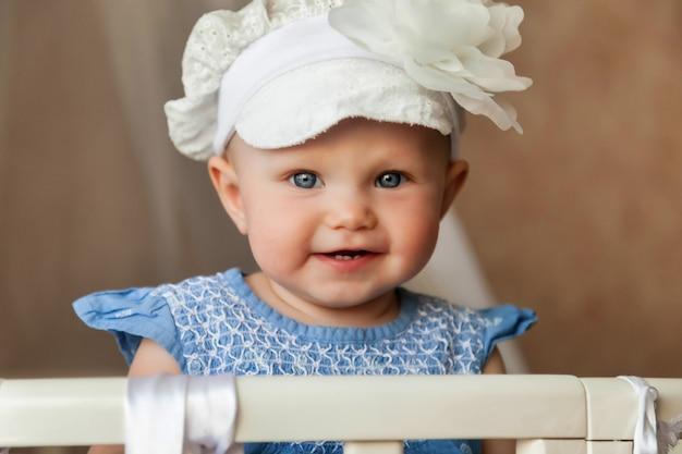 スタイリッシュな帽子をかぶった1歳の青い目の子供は、ベビーベッドからカメラを見てください。子供部屋に座って、お母さんを待っている笑顔で小さくてかわいい赤ちゃん。適切な育成と子供時代の概念