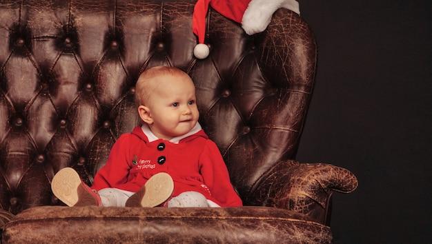 Годовалый ребенок голубыми глазами в рождественском костюме на кресле в гостиной. детские эмоции на античный стул праздничный вечер. концепция семейного празднования рождества и счастливого нового года