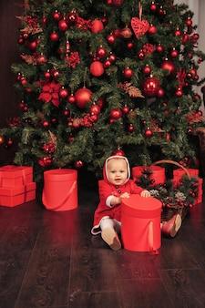 木とプレゼントボックスのあるリビングルームで遊ぶクリスマスの衣装を着た1歳の青い目の子供。感情の休日の夜とかわいい赤ちゃん。クリスマスと新年あけましておめでとうございますの家族のお祝いの概念