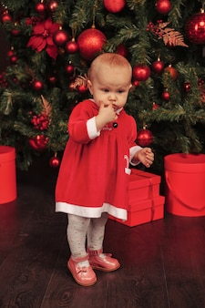 One year old blue eyes child in xmas costume playing in living room with tree and present boxes. cute baby with emotion holiday evening. concept of family celebration of christmas and happy new year