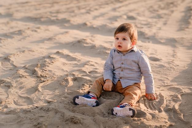 Годовалый мальчик сидит на песке, улыбается и играет.