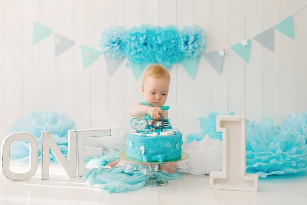 A one-year-old boy tries his first birthday cake