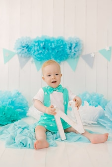 A one-year-old boy with a butterfly in a suit holds the letter n in his hands against the background of festive garlands for a party