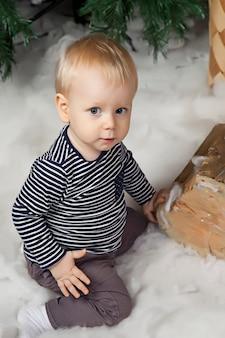 白い毛布に 1 歳の子供がクリスマス ツリーで遊んでいます。クリスマスに飾られた部屋のかわいい男の子