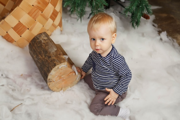 白い毛布の上に 1 歳の子供がメリー クリスマス ツリーで遊んでいます。新年あけましておめでとうございます飾られた部屋でかわいい男の子。