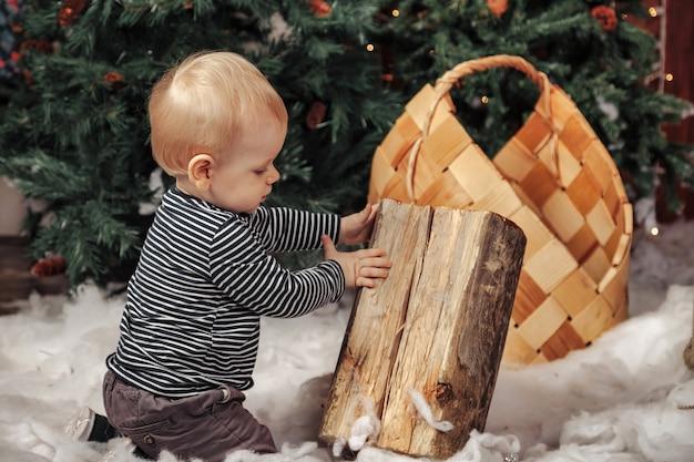 Годовалый ребенок на белом пушистом одеяле, играя у рождественской елки. милый мальчик в гостиной украшенной рождеством. маленький ребенок смотрит в сторону. концепция детей с новым годом. скопируйте место для сайта