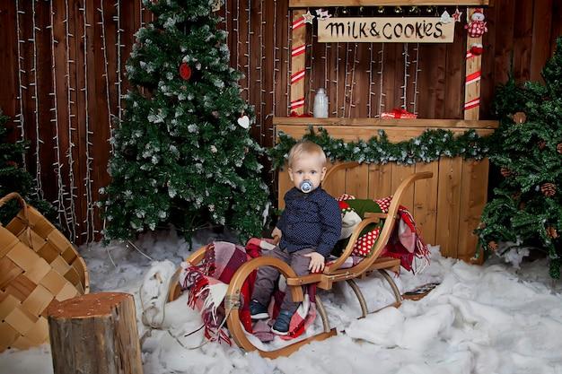 1 歳の子供がクリスマス ツリーでそりで遊ぶ。クリスマスに飾られた部屋のかわいい男の子