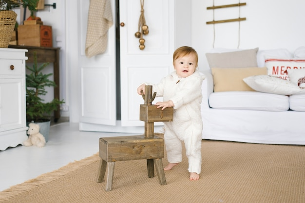 A one-year-old child in a soft jumpsuit stands next to a wooden deer toy in the living room, decorated for christmas or new year