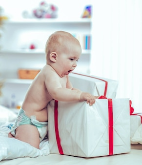 Годовалый милый ребенок играет с покупками в коробках на диване