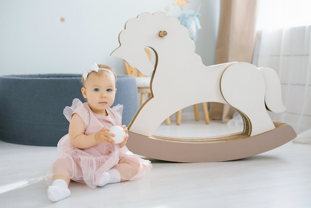 A one-year-old girl in a pink dress holds a white ball in her hands and sits next to a rocking horse toy in a children's room