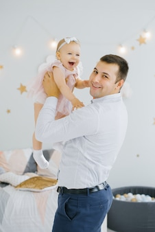 A one year old girl in a pink dress is happy and smiling in dad's arms