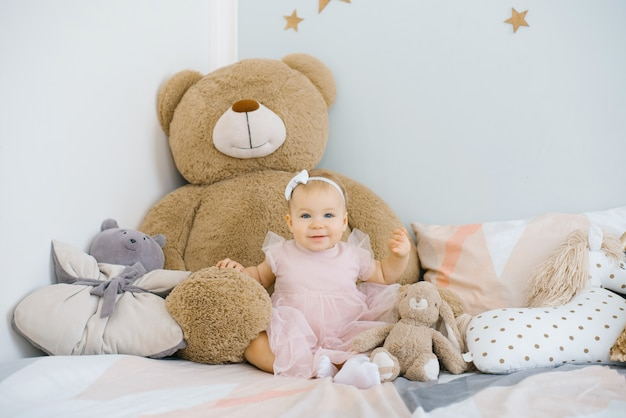 A one-year-old girl in a pink dress sits on the bed surrounded by soft toys and pillows