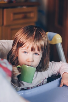 A one-year-old smiling girl sits at a children's table in a high chair and eats with a spoon from a bowl. colored background. healthy eating for kids. baby food.