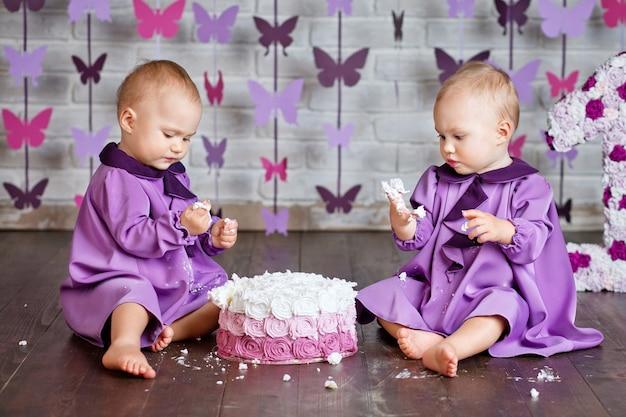 한 살짜리 쌍둥이 소녀가 첫 번째 생일을 선택하고 스매시 케이크를 먹고 있습니다.