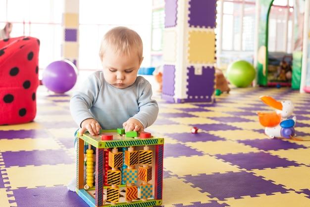 Годовалый мальчик-малыш играет с кубиком мелкой моторики в игровой комнате