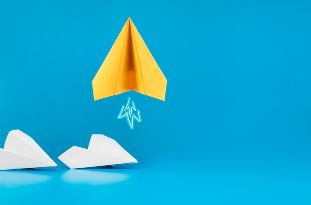 One yellow paper airplane takes off on a blue background