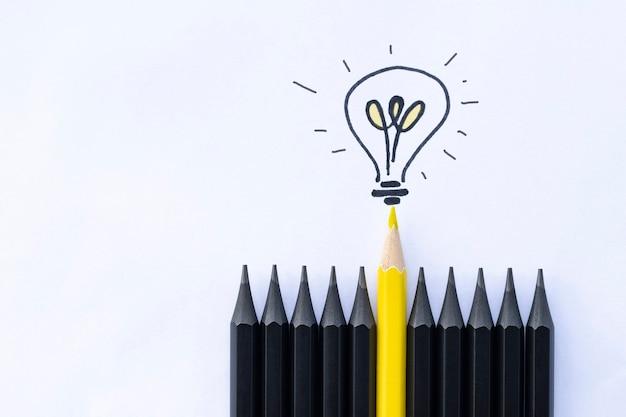 黒い鉛筆の中に電球が付いた黄色の鉛筆1本。ビジネスコンセプト