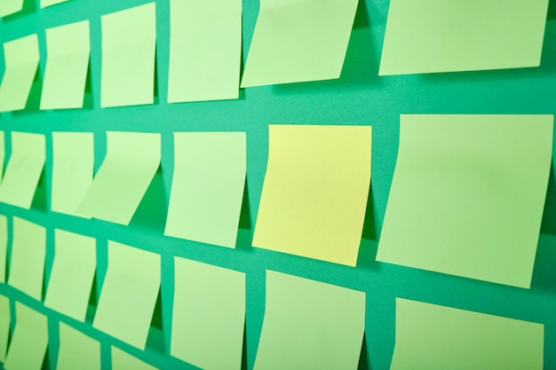 Одна желтая наклейка и множество светло-зеленых заметок на зеленой поверхности