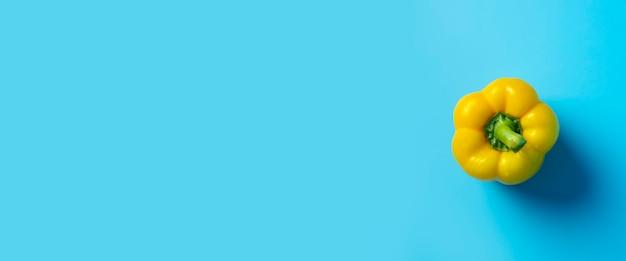 Один желтый сладкий перец на синем фоне. вид сверху, плоская планировка. баннер.