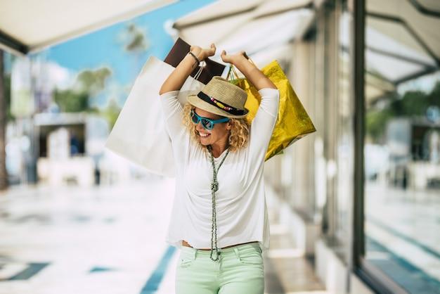 Одна молодая и красивая женщина покупает подарки и одежду и гуляет в торговом центре на открытом воздухе