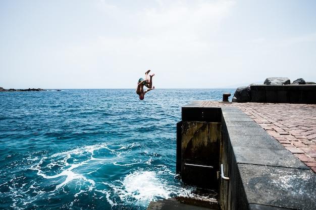 夏の暑い日にビーチで楽しんでいる海や海の水に崖から飛び降りる一人の若くて幸せなティーンエイジャー。屋外でアクティブで美しいライフスタイル