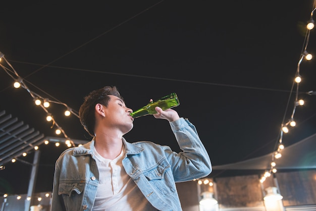 One young asian man drink bottle of beer. side view of handsome hipster men hand holding beer bottle and drink while sitting at the bar counter on rooftop floor of nightclub party at restaurant.