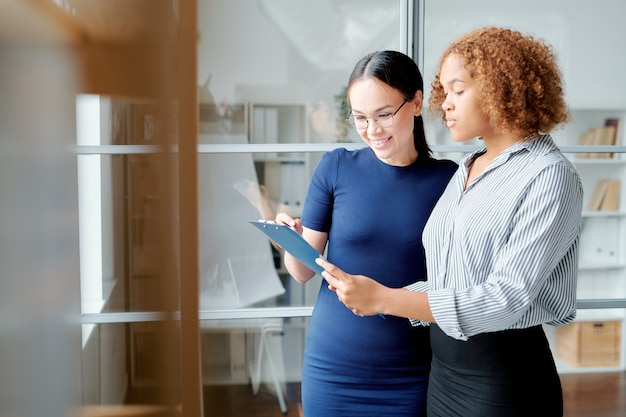 One of young business partners pointing at contract held by colleague while looking through its terms during negotiation