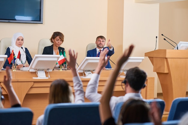 One of young confident delegates pointing at audience for question after his speech during business conference