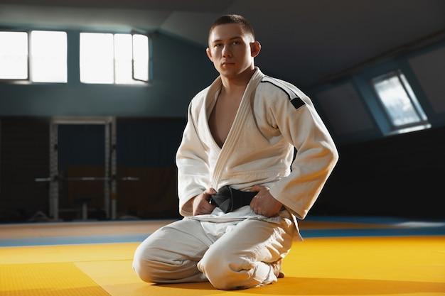 Один молодой боец в кимоно тренирует боевые искусства в спортзале