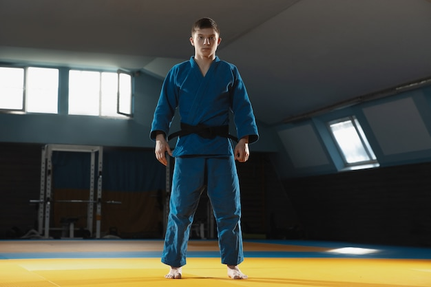 Un giovane combattente in kimono allenamento arti marziali in palestra