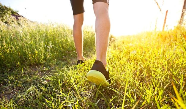 Один молодой человек бегает по пересеченной местности по тропинке на лугу