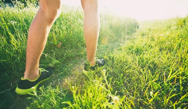 Один молодой человек бежит трусцой по дорожке на лугу.