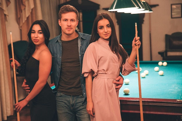 One young man stand beyween two models. they look on camera seriously. young women hold billiard cues in hands. they stand in playing room.