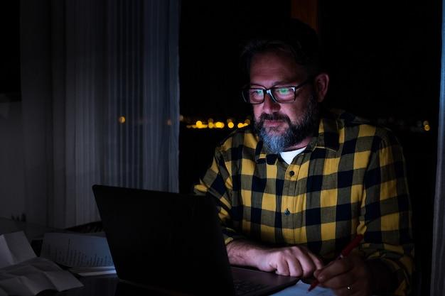 한 젊은이는 노트북을 사용하고 집에서 밤에 컴퓨터 작업을 합니다. 그의 사무실에서 직장에서 사업가