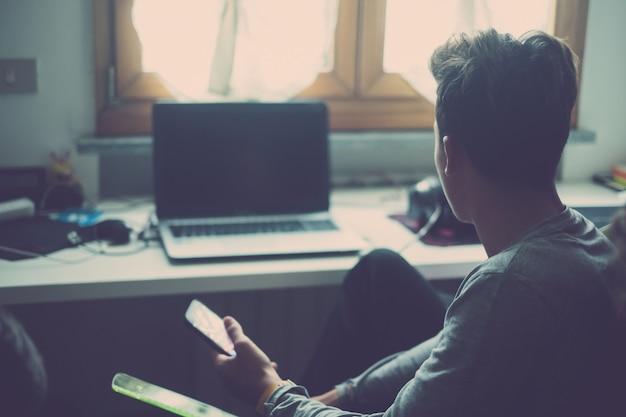 Один молодой человек пользуется телефоном и смотрит на ноутбук или компьютер дома в своей комнате, играя в видеоигры. подросток пристрастился к социальной сети и социальным сетям