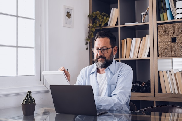 One young man working at home in the office with laptop and notebook taking notes talking in a video conference. one businessman calling communicating
